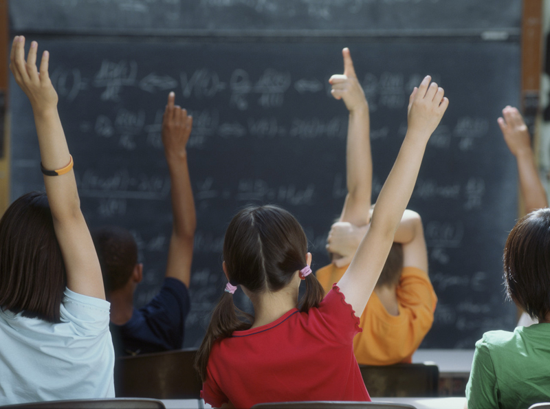 Rear view of class raising hands